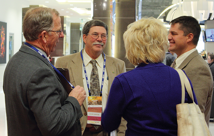 Outgoing WAWG President Larry Cochran (center) speaks with incoming WAWG President Kevin Klein (right) and Benton County grower Nicole Berg.