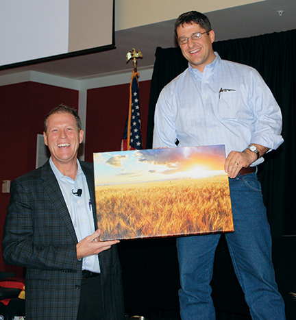 Incoming WAWG President Kevin Klein (right) gives emcee Damian Mason a print of a wheat field as a thank you gift from the three states.