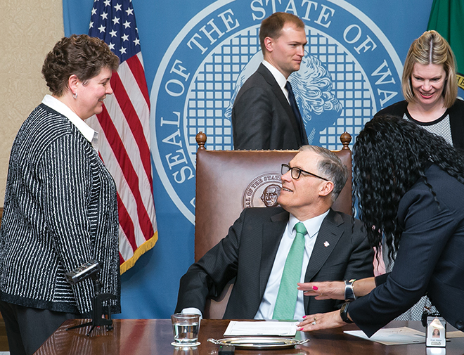 Marci Green (left), vice president of the Washington Association of Wheat Growers (WAWG), speaks with Gov. Jay Inslee during the signing of SSB 5051, a bill that triples the amount of time the Washington State Department of Natural Resources is required to give notice when terminating agricultural or grazing leases early. WAWG lobbyist Diana Carlen (far right) also attended the signing. Photo courtesy of the Washington State Legislative Support Services.